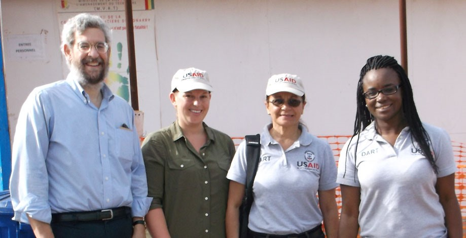 Berzon with DART-USAID colleagues outside an Ebola treatment unit – NOTE: Image is prohibited for reuse