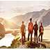 Four friends stands on view point and looking at sunset mountains and river.