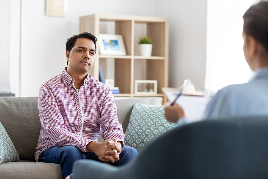 Psychology, mental therapy and people concept - young Indian man patient and woman psychologist at psychotherapy session.