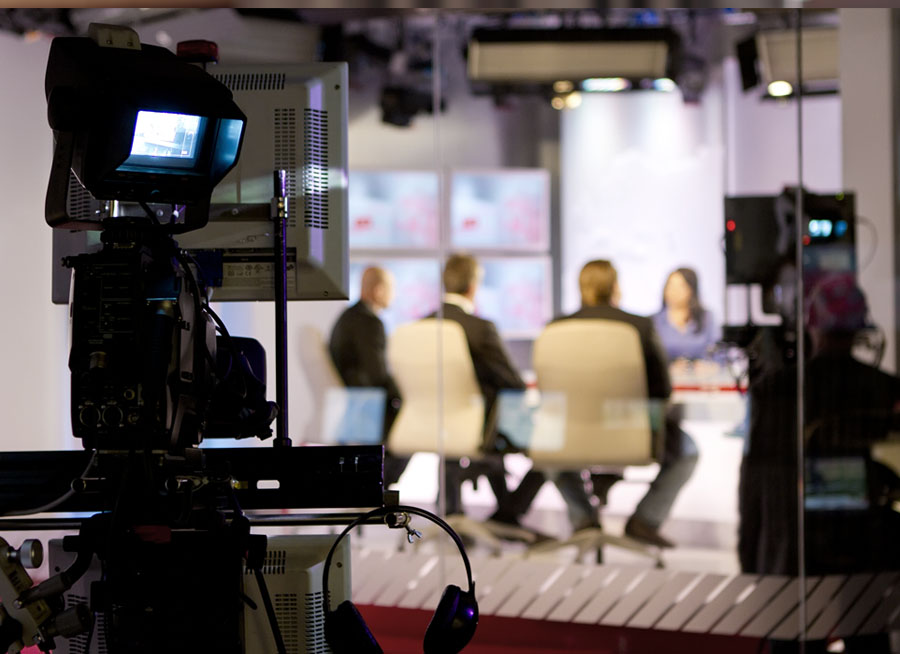Group of people being interviewed on a television set.